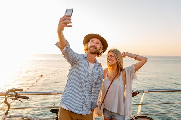 Joven sonriente feliz hombre y mujer viajando en bicicleta tomando selfie foto en la cámara del teléfono Foto gratis