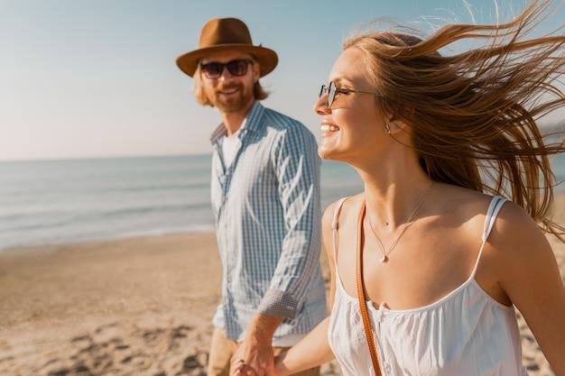 Joven sonriente feliz con sombrero y mujer rubia corriendo juntos en la playa en vacaciones de verano viajando Foto gratis