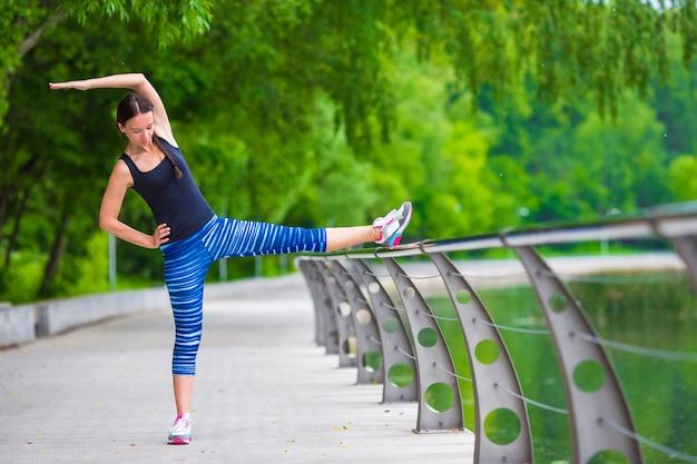 Joven sonriente haciendo ejercicios deportivos al aire libre Foto Premium