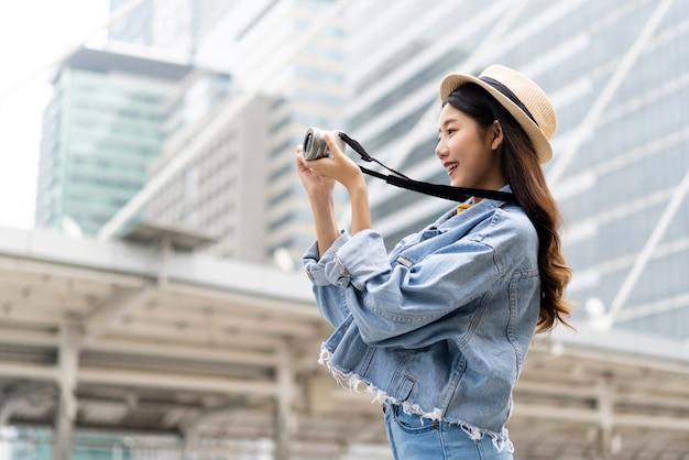 Joven sonriente mujer asiática tomando fotos con la cámara en la ciudad Foto Premium