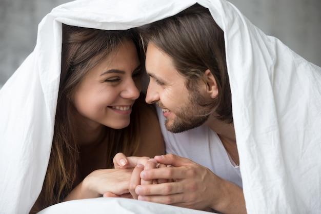 Joven sonriente pareja en la cama divirtiéndose cubierto con manta Foto gratis