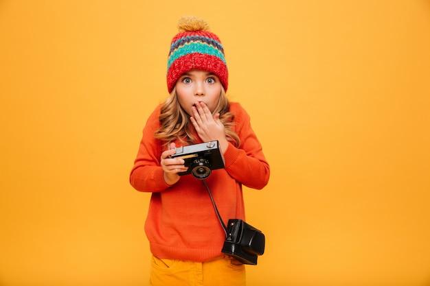 Joven sorprendida en suéter y sombrero con cámara retro y mirando a la cámara sobre naranja Foto gratis
