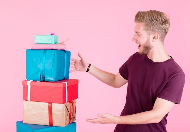 Joven sorprendido mirando la pila de cajas de regalo sobre fondo rosa Foto gratis