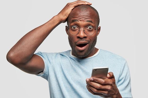 Un joven sorprendido recibe un recordatorio de mensaje en un teléfono inteligente y se olvida de una reunión importante Foto gratis
