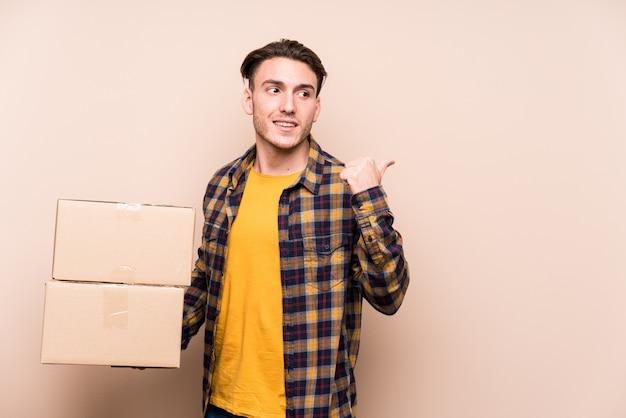 Joven sosteniendo cajas puntas con dedo pulgar lejos, riendo y despreocupado Foto Premium
