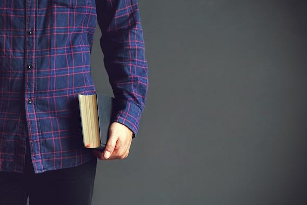 Joven sosteniendo la santa biblia. libro, lectura, biblia. espacio de copia Foto Premium