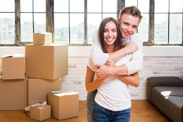 Joven sosteniendo a su novia sonriente Foto gratis