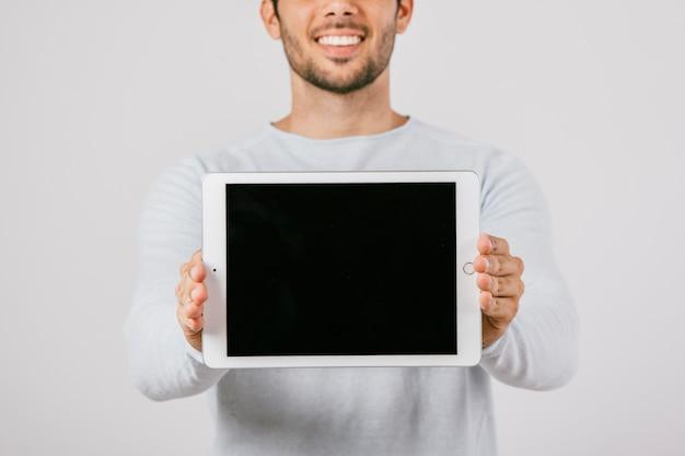Joven con tablet en horizontal Foto gratis