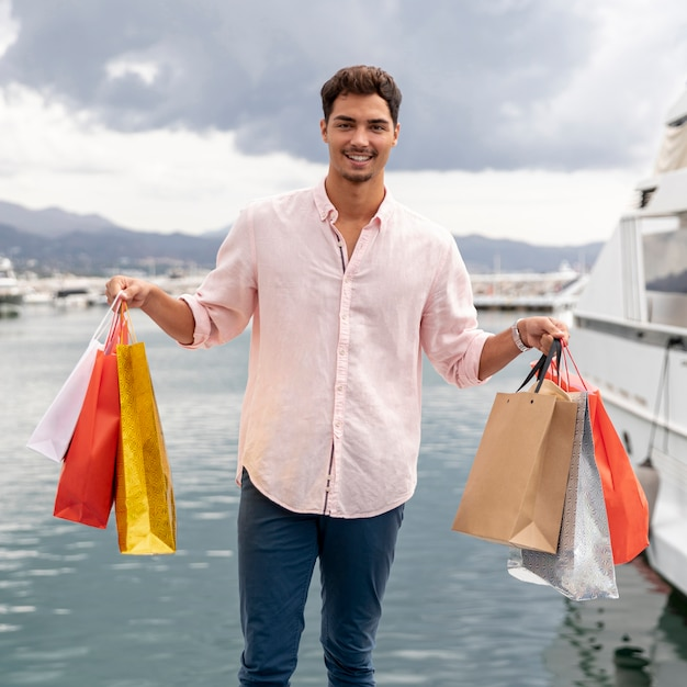 Joven teeanger mostrando sus bolsas de compras Foto gratis