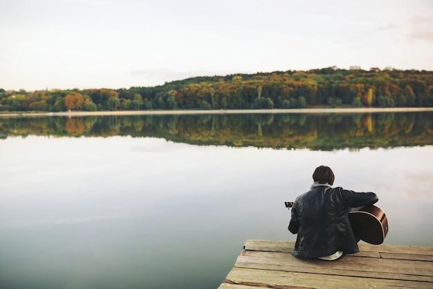 Joven tocando la guitarra en el lago Foto gratis