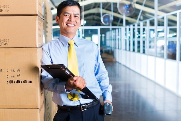 Joven trabajador indonesio en almacén con escáner Foto Premium