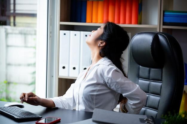 Joven trabajadora dolor de espalda mientras trabaja Foto gratis