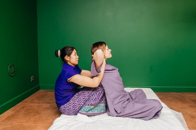 La joven trabajadora masajista tailandesa en traje exótico étnico asiático hace y demuestra diferentes procedimientos de spa tradicionales en la sala de yoga de relajación verde Foto Premium