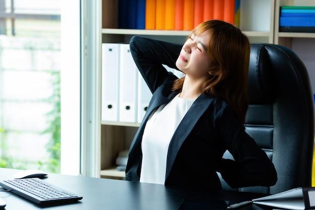 Joven trabajadora siente dolor de espalda en la oficina Foto gratis