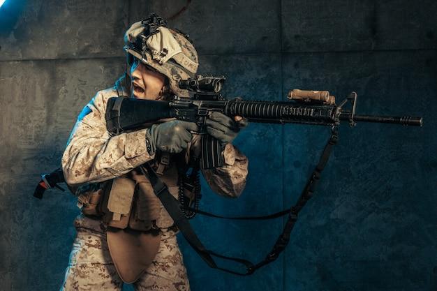 Joven en traje militar un soldado mercenario en los tiempos modernos en una pared oscura en studio Foto Premium