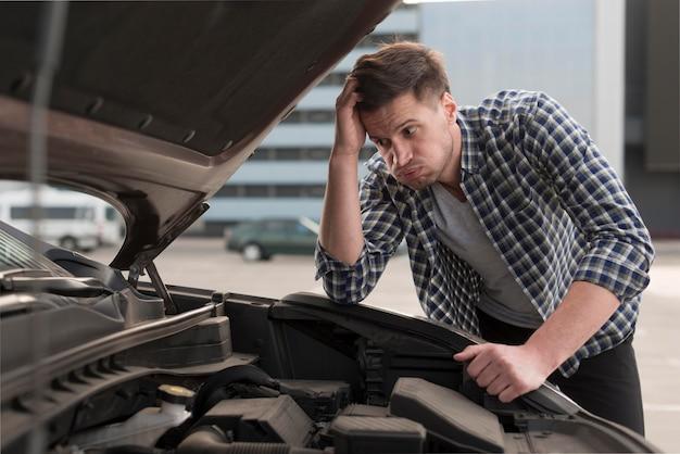 Joven tratando de reparar el auto Foto gratis