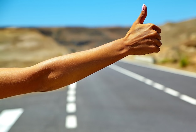 Joven turista caucásico haciendo autostop a lo largo de una carretera en la puesta del sol Foto gratis