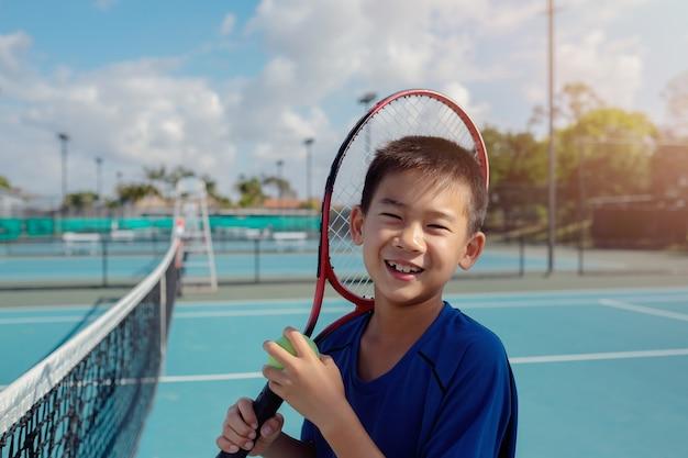 Joven tween jugador de tenis asiático en cancha azul al aire libre ...