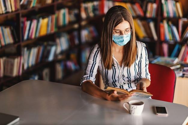 Joven universitaria atractiva con mascarilla sentada en la biblioteca y estudiando durante la pandemia de corona. Foto Premium