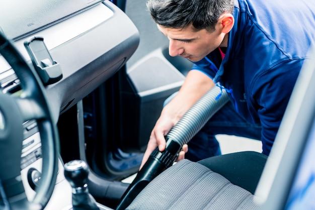 Joven usando aspiradora para limpiar el interior de un auto Foto Premium