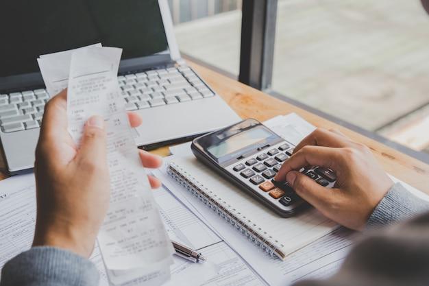 Joven usando la calculadora y calcular las facturas en la oficina en casa. Foto Premium