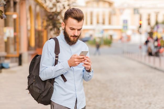 Joven usando teléfono móvil al aire libre Foto gratis