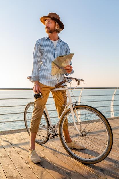 Joven viajando en bicicleta por el mar en vacaciones de verano junto al mar al atardecer, sosteniendo un mapa de turismo con cámara Foto gratis