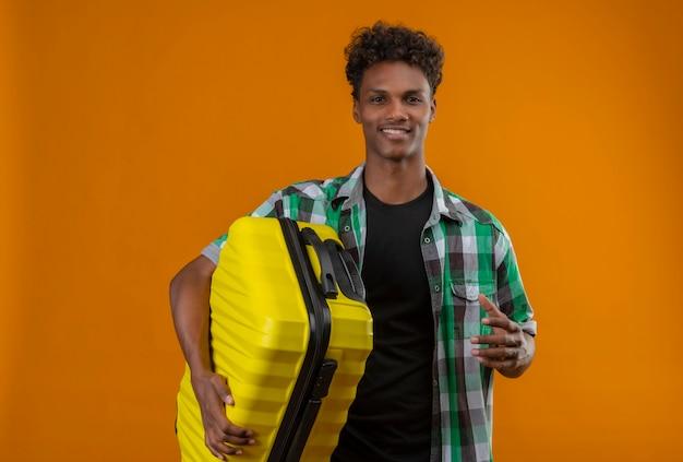 Joven viajero afroamericano hombre sujetando la maleta sonriendo alegremente positivo y feliz mirando a la cámara de pie sobre fondo naranja Foto gratis