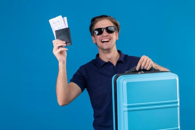 Joven viajero guapo hombre que llevaba gafas de sol negras de pie con la maleta con billetes de avión mirando a la cámara con cara feliz sonriendo alegremente sobre fondo azul Foto gratis
