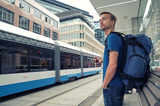 Joven viajero masculino con mochila y teléfono inteligente de pie en la parada de transporte público y esperando el tranvía en el moderno centro de la ciudad. Foto Premium