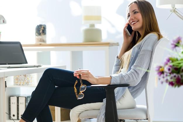 Joven y bella mujer utilizando su tel fono m vil en la for Follando en la oficina gratis