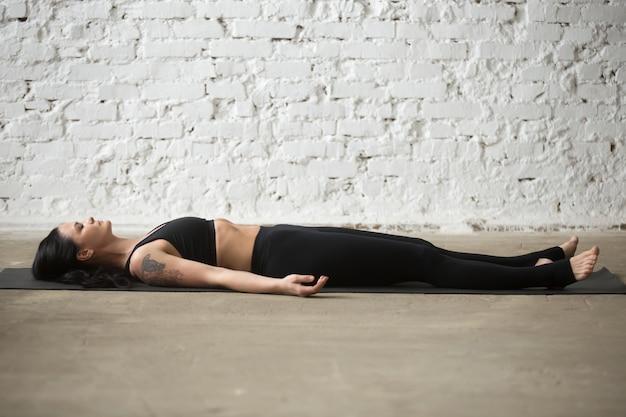 Joven, yogi, atractivo, mujer, savasana, pose, blanco, loft, backgro Foto gratis
