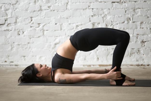 Joven, yogui, atractivo, mujer, glute, puente, pose, loft, backgroun