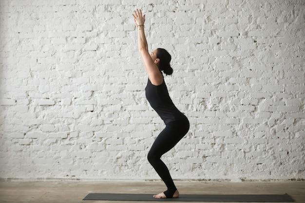 Joven, yogui, atractivo, mujer, silla, pose, blanco, loft, fondo