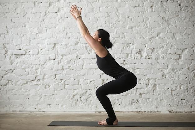 Joven, yogui, atractivo, mujer, utkatasana, pose, blanco, loft, backg