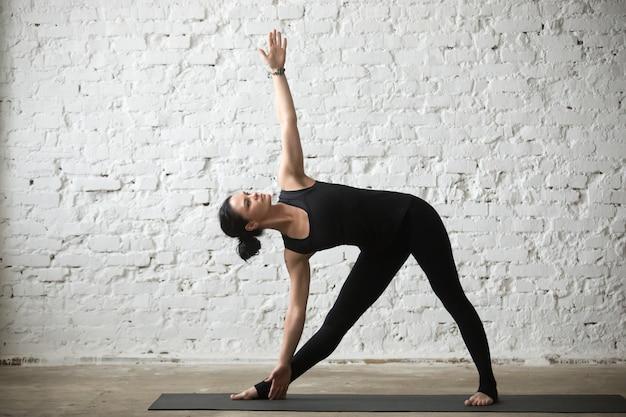 Joven, yogui, atractivo, mujer, utthita, trikonasana, pose, blanco, l