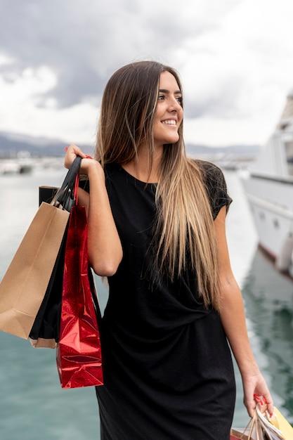 Jovencita con bolsas de compras mirando a otro lado Foto gratis