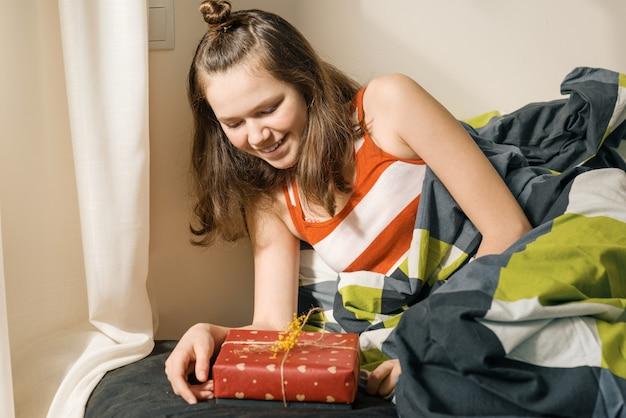 Jovencita mirando y abriendo regalo sorpresa en caja Foto Premium