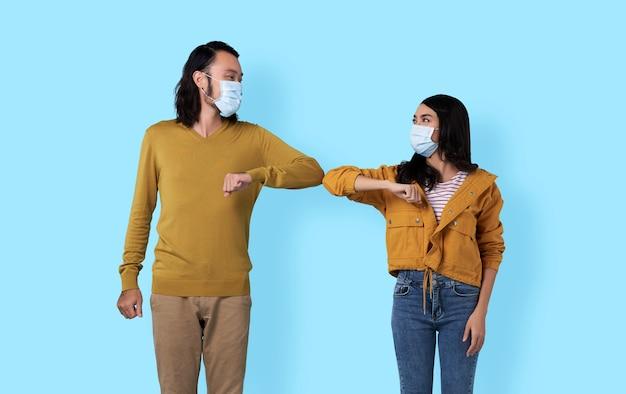 Jóvenes amigos asiáticos que se saludan con los codos. una nueva forma de saludo para evitar la propagación del coronavirus (covid-19). Foto Premium