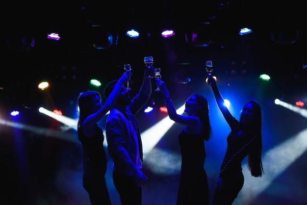 Jóvenes amigos bailando con copas de champagne en las manos. contra dispositivos de iluminación como fondo. los amigos de los jóvenes están bailando. Foto Premium