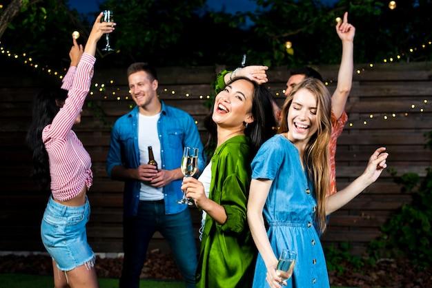 Jóvenes amigos bailando juntos al aire libre Foto gratis