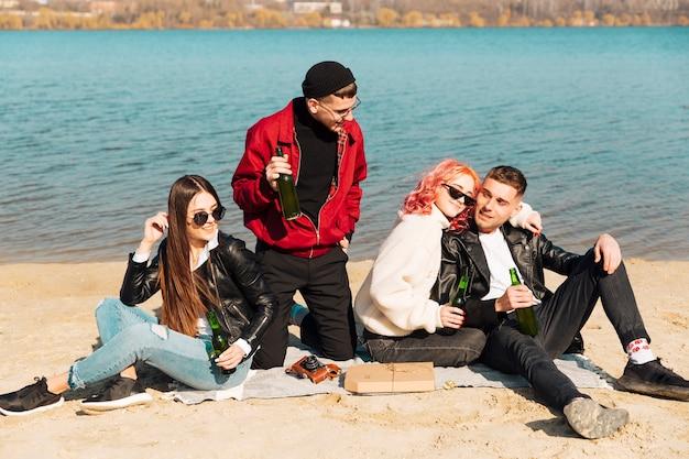 Jóvenes amigos bebiendo cerveza en la soleada playa de primavera Foto gratis