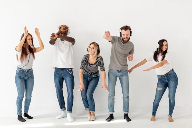 Jóvenes amigos escuchando música y bailando Foto gratis