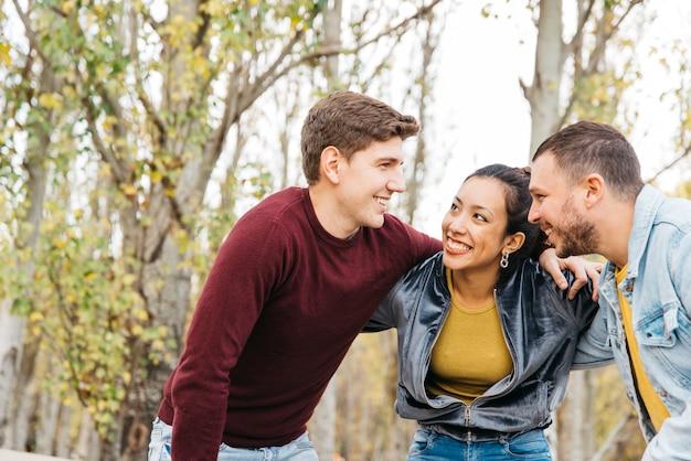 Jóvenes amigos multirraciales de pie con las manos en los hombros Foto gratis