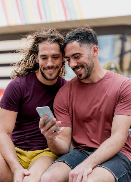 Jóvenes amigos varones mirando móvil Foto gratis