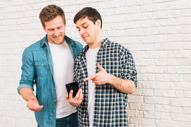 Jóvenes amigos varones que muestran algo en el teléfono móvil a su amigo Foto gratis