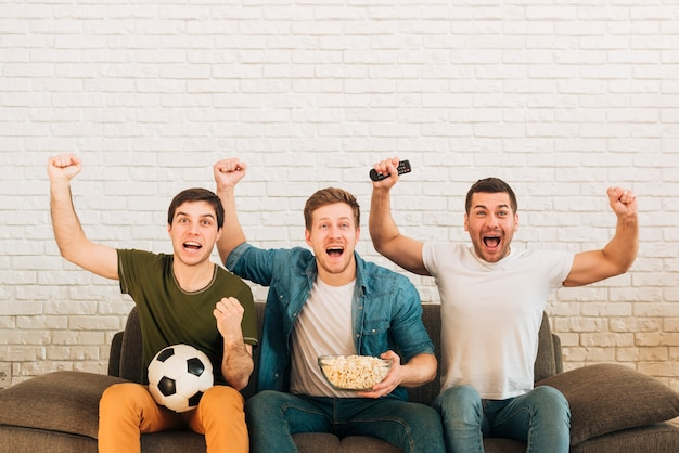 Jóvenes amigos varones vitoreando mientras miran un partido de fútbol en la televisión Foto gratis