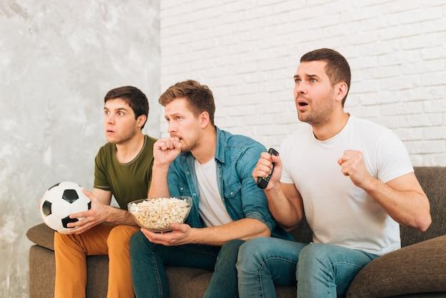 Jóvenes amigos viendo partido de fútbol en televisión con expresiones serias. Foto gratis