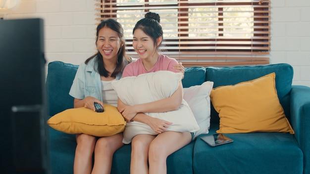 Jóvenes asiáticas lesbianas lgbtq mujeres pareja viendo la televisión en casa Foto gratis