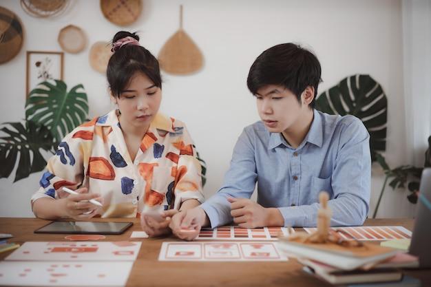 Jóvenes asiáticos creativos desarrolladores de aplicaciones móviles teamworks debate sobre la pantalla de diseño de plantillas móviles para la planificación creativa del desarrollo de aplicaciones móviles. Foto Premium